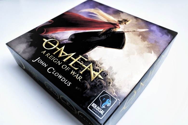 Kickstarter preview omen a reign of war box cover of the kolossal release